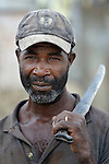 A man holds his machete while returning from field work in Batey Bombita, a community in the southwest of the Dominican Republic whose population is composed of Haitian immigrants and their descendents.