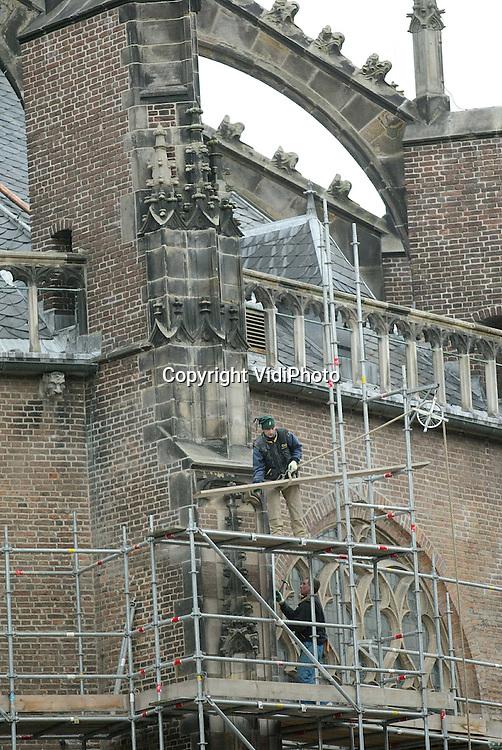 Foto: VidiPhoto..ARNHEM - Steigerbouwers breken de steigerwerken aan de oostzijde de Eusebiuskerk in Arnhem af. Aan de kerk wordt gedurende tien jaar lang groot onderhoud gepleegd. De tweede fase is nu afgerond. In mei start de derde fase. Het totale onderhoud is onderverdeeld in vijf fasen, die ieder twee jaar duren.