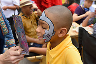 A boy admiring his face painting in a mirror.