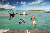 MAURITIUS, Mahebourg, kids do flips off of a retaining wall at the waterfront in Mahebourg at Pointe D'Esny, Ile aux Aigrettes in the distance