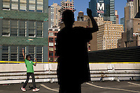 13 years-old Brandon Carter (R) flies a kite from the rooftop of the Port Authority bus terminal in New York City, USA, during the third annual Kite Flight event, 23 September 2007.