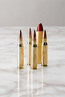 Bullets and lipstick on marble surface