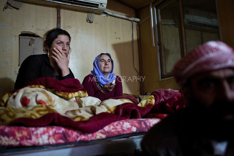 18/02/15 --TANJERO, IRAQ: Hayam (L), Ghazal (C), and Said (C) watch television in the shipping container they call home.<br /> <br /> A family of displaced Yezidis lives next to an oil refinery in the Kurdish Region of Iraq. The men run the refinery 24 hours a day with little to no safety equipment. Reporting for this article was supported by a grant from the Pulitzer Center on Crisis Reporting