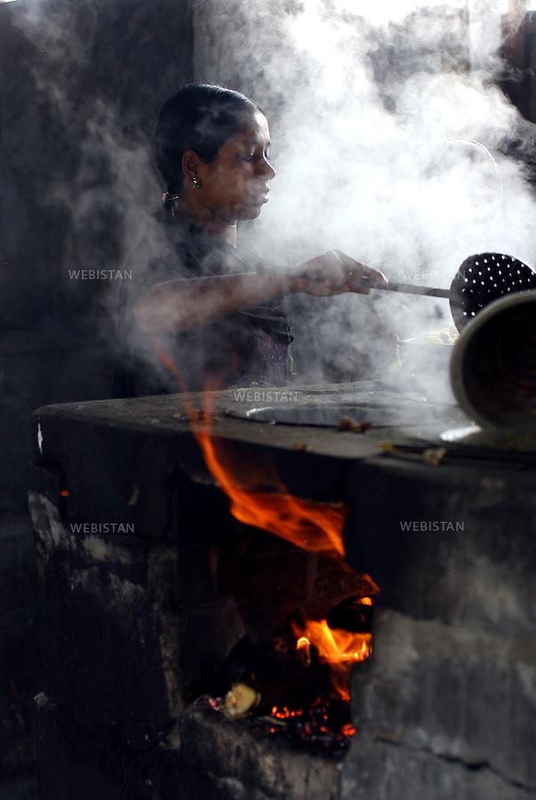 Bangladesh. A woman boils the cocoons which then will yield threads. ..Bangladesh. Une femme fait bouillir les cocons qui produiront ensuite des fils.