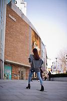 Una donna nella zona commerciale della città.<br /> A woman walking in the commercial area of the city