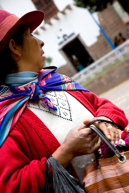 A PERUVIAN WOMAN CLUTCHES HANDBAG ON THE STREETS OF CUZCO,PERU