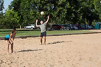 A young athlete serving and playing volleyball on Zilker Park sand volleyball courts on a beautiful sunny day in Austin, Texas.