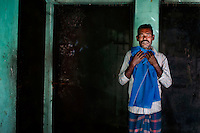 Modhu Miyha holds a dress of his daughter Moksuda (18) who died in the Tazreen Fashions factory fire. He poses for a portrait in front of the burnt living room next to the factory building in Ashulia, Bangladesh.