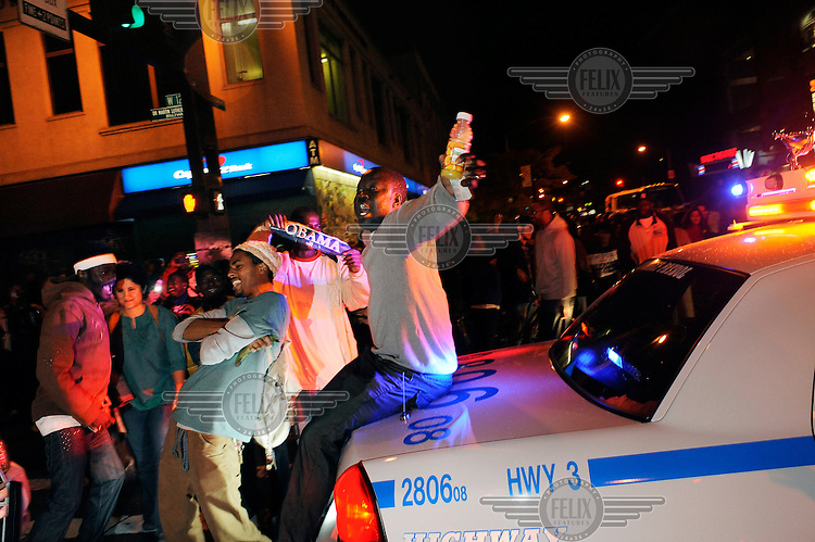 A man sits on the boot of a highway patrol vehicle as celebrations in Harlem continue into the night after Barack Obama was named the winner of the 2008 Presidential elections..