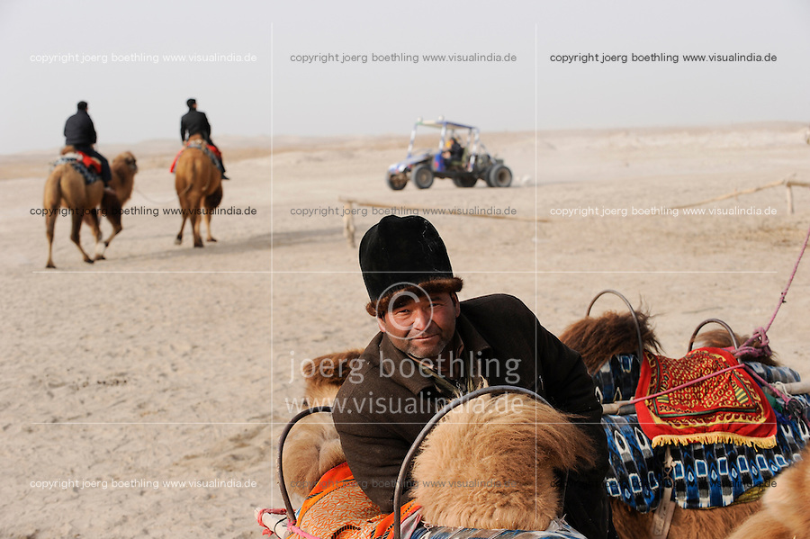 "Asien CHINA Provinz Xinjiang Han chinesische Touristen und uigurischer Kameltreiber am Dawakun See in Taklamakan Wueste im Winter  | .Asia CHINA province Xinjiang , Han chinese Tourist und uighur camel driver at Dawakun lake in Taklamakan desert in winter season .| [ copyright (c) Joerg Boethling / agenda , Veroeffentlichung nur gegen Honorar und Belegexemplar an / publication only with royalties and copy to:  agenda PG   Rothestr. 66   Germany D-22765 Hamburg   ph. ++49 40 391 907 14   e-mail: boethling@agenda-fototext.de   www.agenda-fototext.de   Bank: Hamburger Sparkasse  BLZ 200 505 50  Kto. 1281 120 178   IBAN: DE96 2005 0550 1281 1201 78   BIC: ""HASPDEHH"" ,  WEITERE MOTIVE ZU DIESEM THEMA SIND VORHANDEN!! MORE PICTURES ON THIS SUBJECT AVAILABLE!! ] [#0,26,121#]"