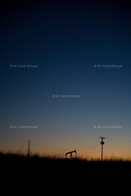 An oil pump is silhoutted against the dawn sky near Sumatra, Montana, USA.