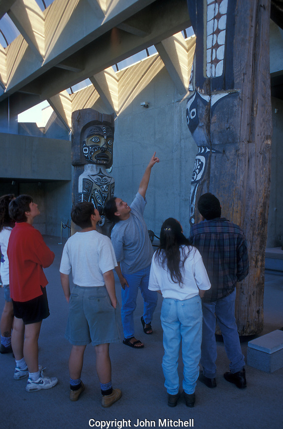 Native Indian guide and visitors in the Great Hall of the Museum of Anthropology on the campus of the University of British Columbia, Vancouver, Canada