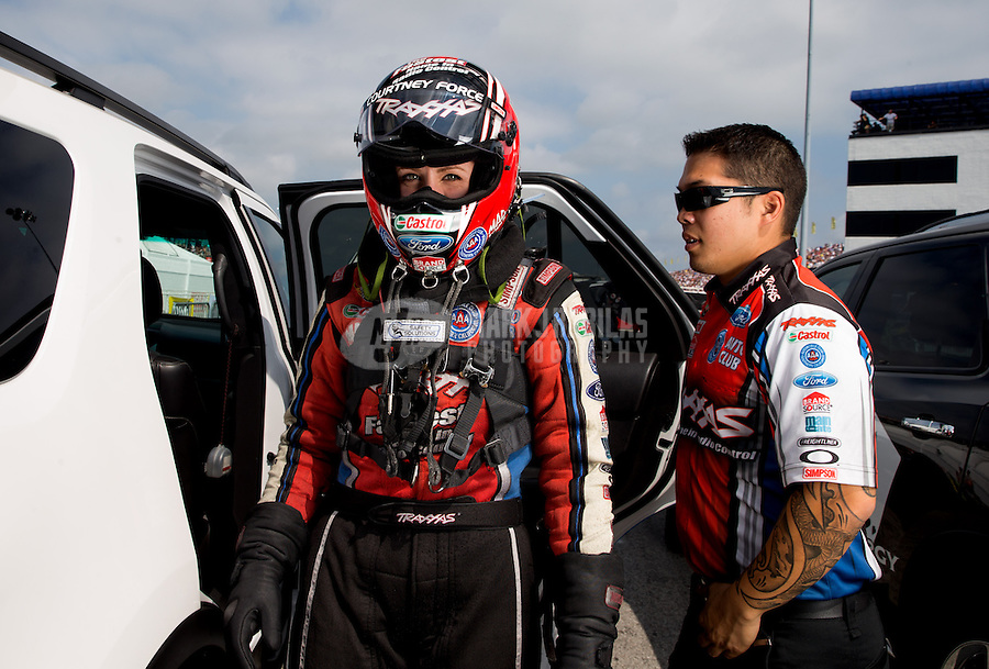 Sept. 1, 2013; Clermont, IN, USA: A crew member with NHRA funny car driver Courtney Force during qualifying for the US Nationals at Lucas Oil Raceway. Mandatory Credit: Mark J. Rebilas-