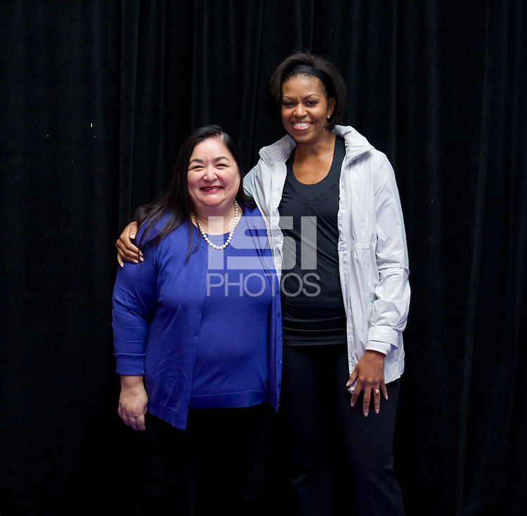 First Lady Michelle Obama stands with US Soccer Foundation Director and President and Chief Executive Officer of the National Alliance for Hispanic Health Jane Delgado during a US Soccer Foundation clinic held at City Center in Washington, DC.