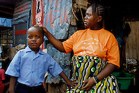 Kroo Bay, Freetown, Sierra Leone...Story on child and maternal health in the Kroo Bay slum community in Freetown, Sierra Leone, which has the World's worst infant and maternal mortalitly rates. One in 4 children die before they reach the age of 5 and one in 6 mothers dies during child birth (in the UK, the rate is one in 3,800)...The Kroo Bay Community Health Centre has a catchment area of over 8,000 people but lacks adequate facilites to provide even basic care. The clinic lacks even the basics, such as bedpans, surgical spirits and cotton wool. It has no electricity and clean drinking water must be fetched from the nearby well everyday...Aminata Kamara (28) with her first born, Musa Conteh (4), outside their home. Musa has just returned from School...© 2007 Aubrey Wade. All rights reserved.