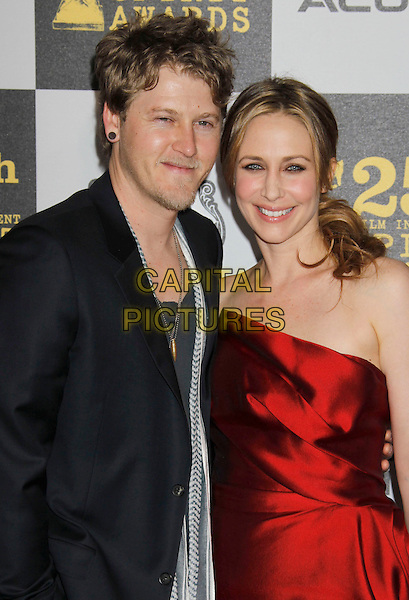 RENN HAWKEY & VERA FARMIGA .25th Annual Film Independent Spirit Awards - Arrivals held at the Nokia Event Deck at L.A. Live, Los Angeles, California, USA, 5th March 2010..indie half length strapless red earring smiling navy blue jacket blazer .CAP/ADM/MJ.©Michael Jade/AdMedia/Capital Pictures.