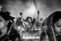 A Hindu woman raises her arms in prayer during the Kartik Brati or Rakher Upobash religious festival in Barodi,  Near Dhaka, Bangladesh