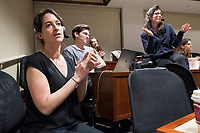 """Monica Giannone (from left in foreground), 29, Brandon Kappy, 26, and Jesse Erin Posner, 27, talk in the back of the room after New York Assemblyman (79th District) and Vice Chair of the Democratic National Committee Michael Blake spoke to a live audience during a session of Resistance School in the Starr Auditorium in the Belfer Building of Harvard University's John F. Kennedy School of Government, on Thurs., April 27, 2017. The three are involved in the production of Resistance School: Giannone is one of the organization's co-founders and is in charge of logistics, content, and tech, during the livestreams; Kappy is the group's Digital Director; and Posner is a production designer. Giannone is a Master in Public Policy grad student at the Kennedy School. Kappy is an MD and MPP student. Posner works in Harvard's Department of Visual and Environmental Studies.  Blake's lecture was titled """"How to sustain the resistance long term.""""  The lecture, which was the fourth such session and the final in what the group calls the """"first semester"""" of Resistance School, was also streamed live on the internet. Resistance School was started by progressive graduate students at Harvard after the Nov. 8, 2016, election of President Donald Trump. Resistance School describes itself as a """"practical training program that will sharpen the tools [needed] to fight back at the federal, state, and local levels."""" The live lectures are streamed and archived online alongside other information on the Resistance School website. During the lectures, teams of volunteers engage with followers on social media, including Facebook and twitter, sharing soundbytes, quotations, and supplementary materials as the lectures happen."""