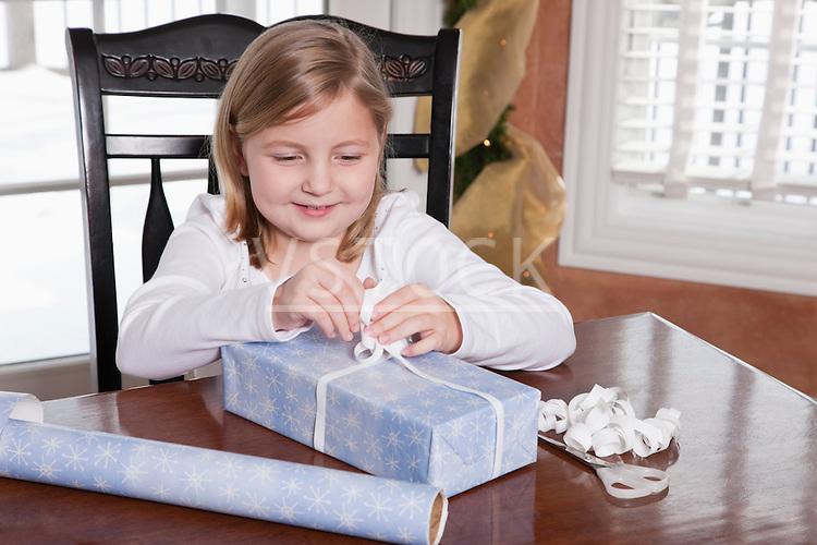 USA, Illinois, Metamora, girl (6-7) wrapping Christmas present