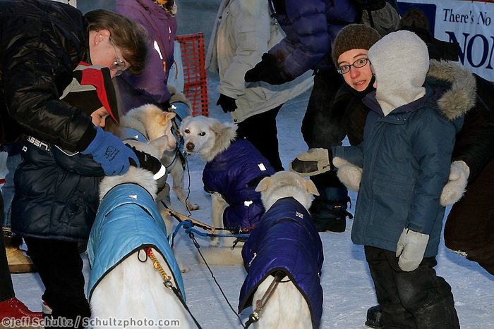 Thursday  March 15, 2007   ---- Nome, Alaska.     Race fans congratulate and pet Jim Lanier's dogs after his arrival in Nome.