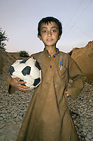 A boy holding a punctured football.