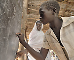 A boy writes on the blackboard under his teacher's careful watch in a school in the Dereig Camp for internally displaced persons.
