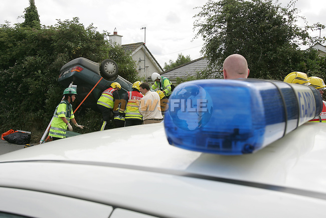 Members of the Drogheda Fire Service with EMT's from Drogheda had to use cutting equipment to remove the driver of the overturned toyota Corolla at the junction in Mornington Co Meath at Lunchtime on Wednesday. The Car hit the ditch and barrel rolled onto its roof traping the driver inside..Photo: Fran Caffrey/ Newsfile.