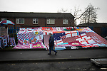 A woman walking past a display of home club flags on Harry Potts Way outside the stadium before Burnley hosted Everton in an English Premier League fixture at Turf Moor. Founded in 1882, Burnley played their first match at the ground on 17 February 1883 and it has been their home ever since. The visitors won the match 5-1, watched by a crowd of 21,484.