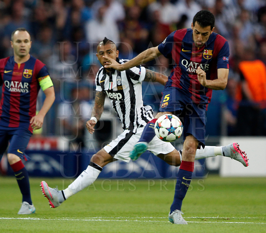 Calcio, finale di Champions League Juventus vs Barcellona all'Olympiastadion di Berlino, 6 giugno 2015.<br /> FC Barcelona's Sergio Busquets, right, kicks the ball as he is challenged by Juventus' Arturo Vidal during the Champions League football final between Juventus Turin and FC Barcelona, at Berlin's Olympiastadion, 6 June 2015. Barcelona won 3-1.<br /> UPDATE IMAGES PRESS/Isabella Bonotto