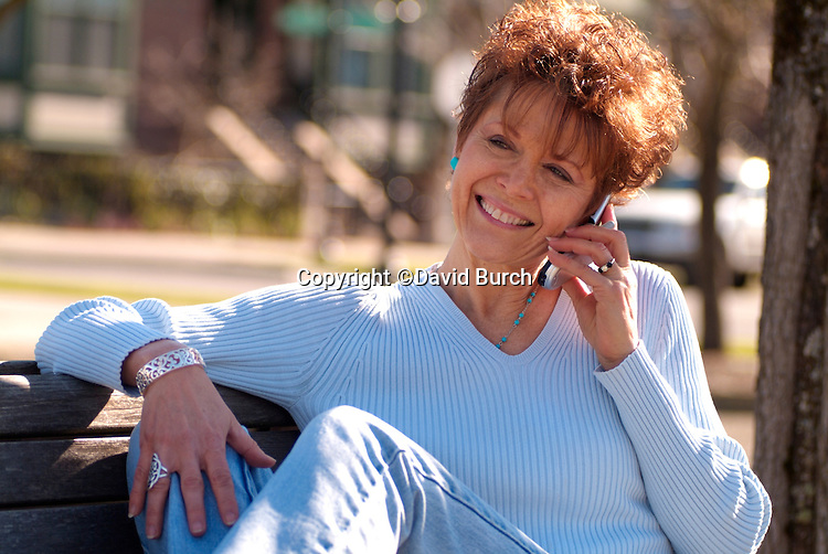 Redheaded woman talking on cell phone in park