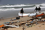 Members of Palestinian security forces inspect the remains of an Egyptian fishermen's boat, which was destroyed during a winter storm off the beach of the central Gaza Strip, January 17, 2019. Photo by Ashraf Amra
