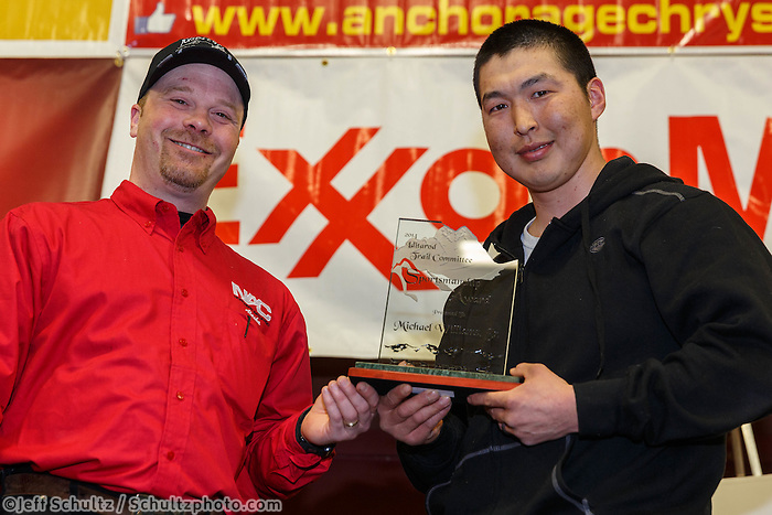 Aaron Burmeister presents the Sportsmanship Award to Mike Williams Jr. at the musher 's finishers banquet in Nome on Sunday March 16 after the 2014 Iditarod Sled Dog Race.<br /> <br /> PHOTO (c) BY JEFF SCHULTZ/IditarodPhotos.com -- REPRODUCTION PROHIBITED WITHOUT PERMISSION