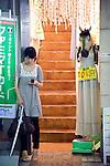 A young woman stands at the entrance of a clothes store in Shimokitazawa, Setagaya Ward, Tokyo, Japan..Photographer: Robert Gilhooly