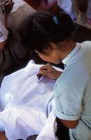 Indonesia, Java island; artisan working on a batik, after preparation of the design,she  applies the wax melted on the parts that do not have to be painted,  so that it penetrates the fibers of the fabric, preventing the waterproof color to adhere, using a tool called a canting ( tjanting).<br /> Indonesia, isola di Giava,artigiana lavora su un batik, dopo la preparazione del disegno, applica la cera sciolta sulle parti che non si vogliono colorare in modo che questa, penetrando tra le fibre del tessuto, le impermeabilizzi impedendo al colore di aderirvi, si utilizza un attrezzo chiamato canting (tjanting).