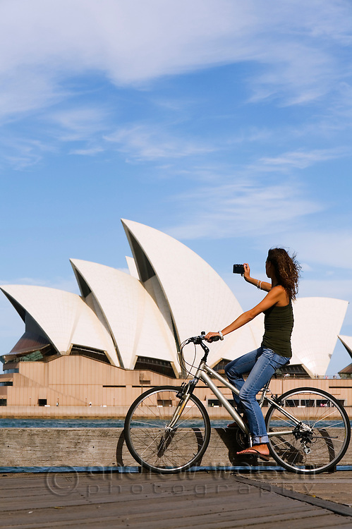 A woman cycling around Sydney Cove photographs the Opera House.  Sydney, New South Wales, AUSTRALIA.
