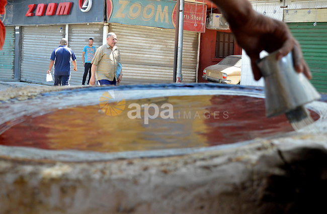 """An Egyptian man prepares a traditional sweets """"Konafa"""" on the holy month of Ramadan, in Cairo, Egypt, on June 12, 2016. Ramadan is sacred to Muslims because it is during that month that tradition says the Koran was revealed to the Prophet Mohammed. The fast is one of the five main religious obligations under Islam. More than 1.5 billion Muslims around the world will mark the month, during which believers abstain from eating, drinking, smoking and having sex from dawn until sunset. Photo by Amr Sayed"""