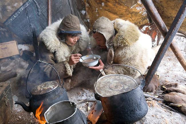 At mealtime in their Yaranga, Chukchi reindeer herders, Grisha Rahtyn & Natasha Nomro, share a bowl of hot reindeer stew. Chukotskiy Peninsula,  Chukotka, Siberia, Russia.