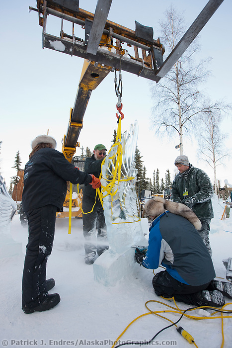 "Jeff Stahl and Heather Brice, USA, get assistance from a crane to hoist the wings on the multi block sculpture titled ""Guardian Angel of Mischief"" for the 2009 World Ice Art Championships in Fairbanks, Alaska. Team members: Heather Brice, Kevin Gregory, Jeff Stahl, Steve Cox"