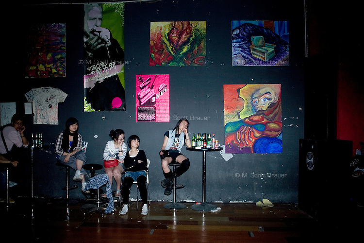 Punk fans sit by a wall at Live Bar at 2 a.m. at the end of a 6 or 7 hour concert in Shanghai, China.