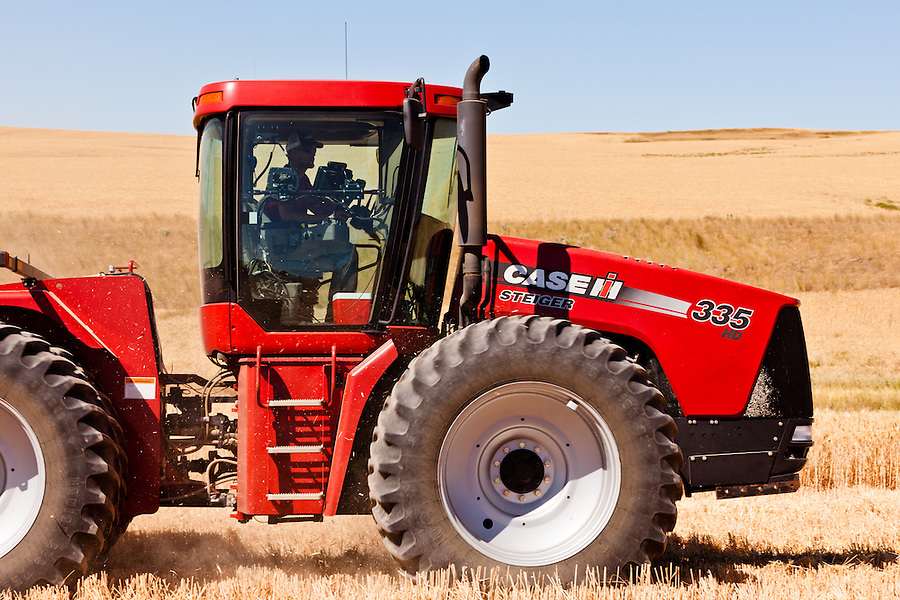 A Case 335 tractor sits in a harvested wheat field with the operator in the cockpit.