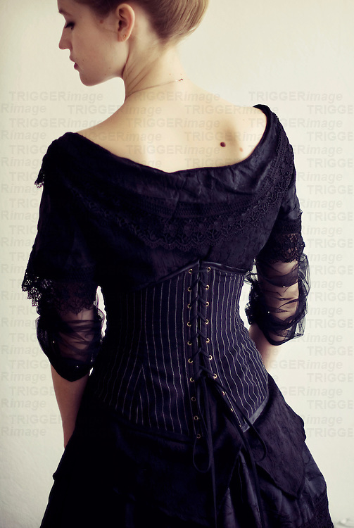 Portrait of young woman in black victorian dress with corset turned away from the camera