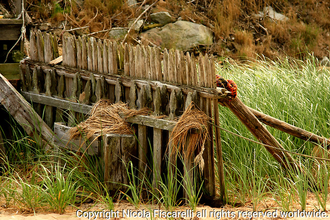 An old weathered wooden fence standing on the beach of  Yarmouth Cape Cod.