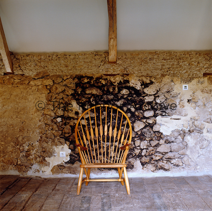 A wooden armchair stands against a stone wall in the granary