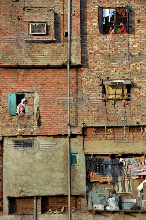 People look out of their windows in a slum in the area of Nizamuddin East.