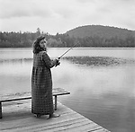 A barefoot woman fishing on a dock in her bathrobe in the Adirondacks of New York