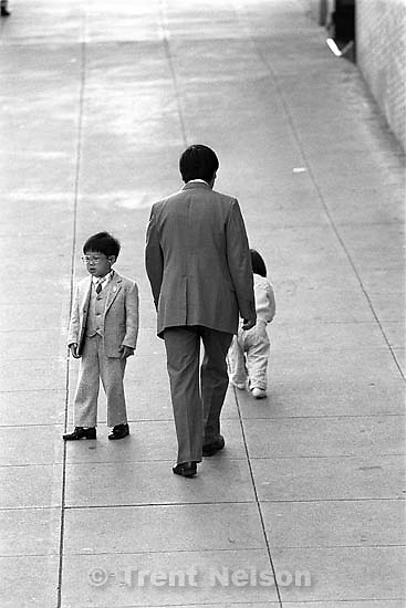 Father and two kids walking down sidewalk.<br />
