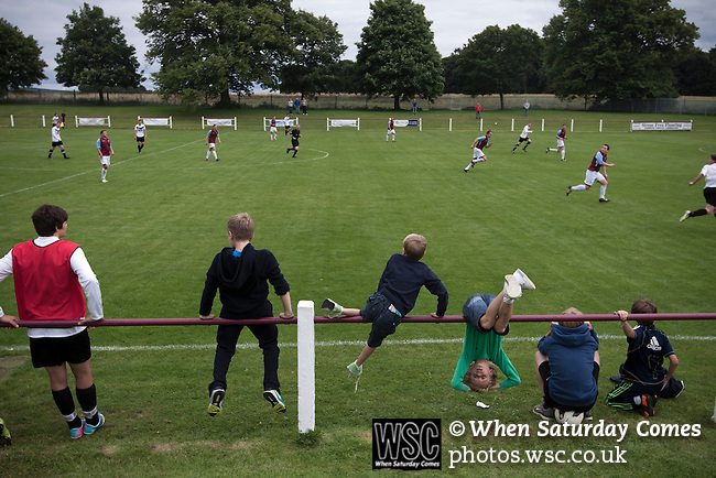 Whitehall Welfare 4 Gala Fairydean 2, 10/08/2013. Ferguson Park, Lowland Football League. Young spectators watching Gala Fairydean Rovers (in white) in action during their team's inaugural match in the Scottish Lowland Football League away to Whitehill Welfare at Ferguson Park. Gala were formed in 2013 by an a re-amalgamation of Gala Fairydean and Gala Rovers, the two clubs having separated in 1908 and Gala's Netherdale ground in Galashiels in the Scottish Borders had one of only two stands designated as listed football stands in Scotland. Whitehill won the match, the first-ever in the newly-formed Lowland League by 4 goals to 2. Photo by Colin McPherson