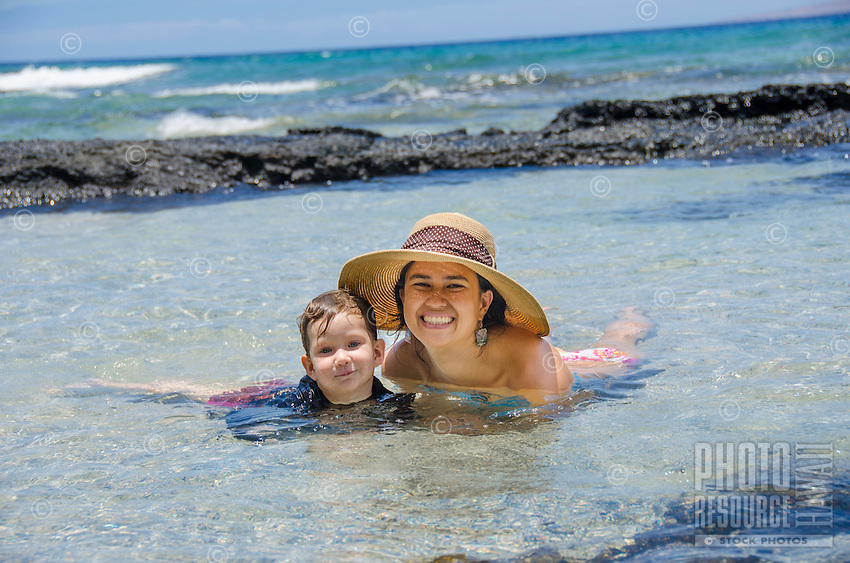A local mother and daughter enjoy the tide pools at a beach in Puako, South Kohala, Hawai'i Island.