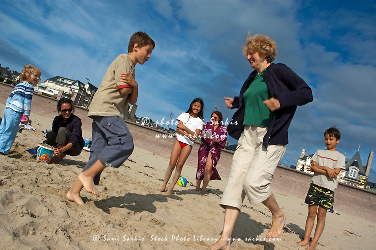 Family playing games on the beach, Brittany, France.