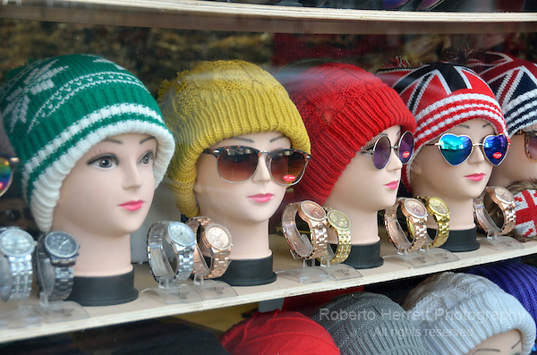Display of women's wooly hats on mannequins in a fashion shop window.